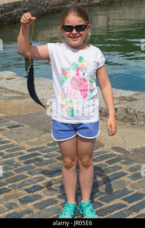 Young girl standing holding fish at Lyme Regis, Dorset in July - Stock Photo