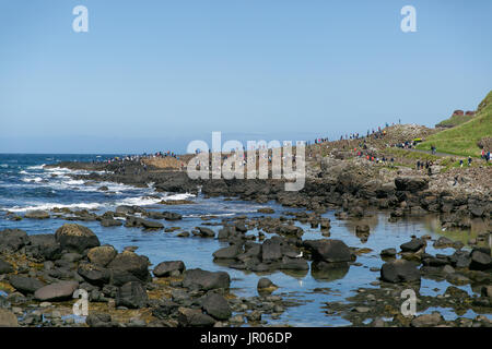 View on the Giant`s Causeway coast stretching out to the Atlantic ocean occupied by tourists and visitors Bushmills Antrim Northern Ireland
