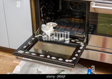 Open oven lid with cleaning material - Stock Photo