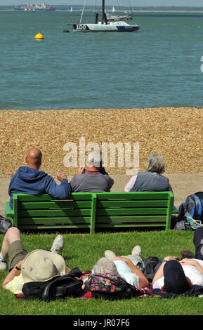 Three older or elderly people sitting on a bench watching the sea and boats with three people laying on the grass - Stock Photo