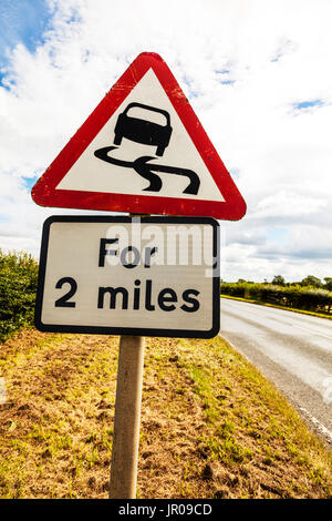 Slippery road, Slippery road UK road sign, for 2 miles, Slippery road for 2 miles, road sign, warning, danger, beware, - Stock Photo