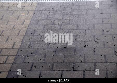 dirty sidewald of paving stones after heavy rainfall, rainwater and flood on a road - Stock Photo