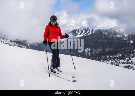 A Female Downhill Skier Poses For The Camera On A Ski Hill At A Ski Resort; Whistler, British Columbia, Canada - Stock Photo