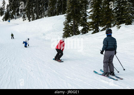 A Group Of Skiers And Snowboarders Making Their Way Down A Hill; Whistler, British Columbia, Canada - Stock Photo