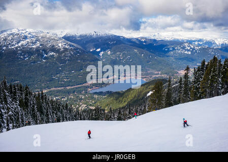 Skiers And Snowboarders Making Their Way Down A Ski Hill With A Magnificent View Of A Lake And The Canadian Rocky - Stock Photo
