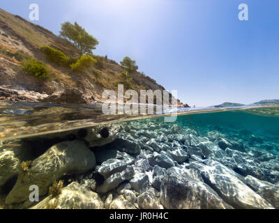 Half underwater in the sea with rocks and sea urchins. - Stock Photo