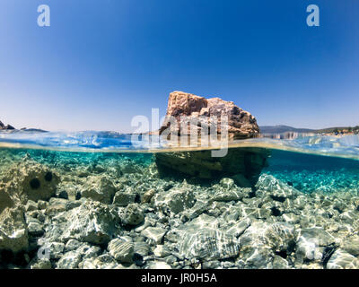 Half underwater in the sea a big rock and small rocks and sea urchins. - Stock Photo