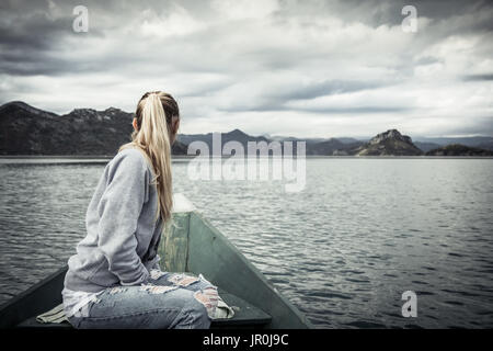Pensive young woman tourist looking at beautiful landscape on   bow of boat floating on water  towards shore in - Stock Photo