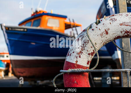 Close-Up Of A Weathered Life Preserver And A Fishing Boat In The Background; Seahouses, Northumberland, England - Stock Photo