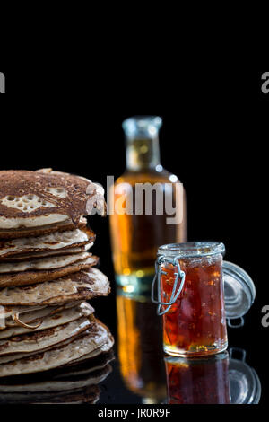 Glutten-free pancakes with jam and Maple syrup, bio healthy ingredients, on black - Stock Photo
