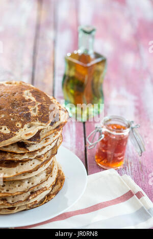 Glutten-free pancakes with jam and Maple syrup, bio healthy ingredients, on kitchen background - Stock Photo