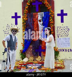 Couple dressed in traditional costume, with homemade shrine to dead and sign about feminicidios. All Souls Day, - Stock Photo
