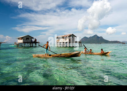 Semporna, Malaysia - 18 April, 2015: Young Bajau laut boy paddling a boat near stilted houses off the coast of Borneo - Stock Photo