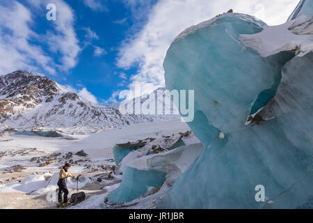A Man Pauses To Eat A Snack While Exploring The Moraine Of Black Rapids Glacier On Skis In The Winter. - Stock Photo