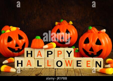 Happy Halloween wooden blocks with candy corn and jack o lantern holders on an orange and black background - Stock Photo