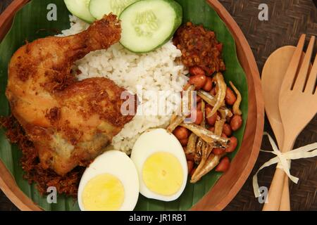 Nasi Lemak, Malaysian Savory Rice Dish with Fried Chicken, Egg, Peanuts, Anchovies, and Chili Paste - Stock Photo
