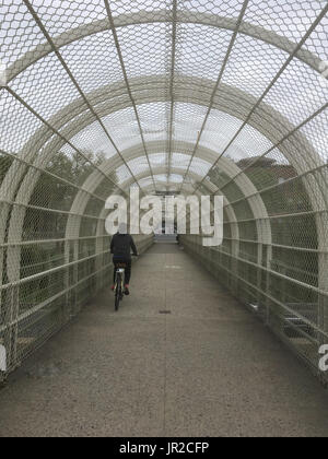 Girl in black rides a bike in a tunnel over a highway in Brooklyn New York. Alternative transportation to cars, - Stock Photo