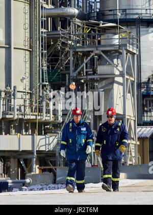 Two Tradesman Walking Together At A Refinery; Edmonton, Alberta, Canada - Stock Photo