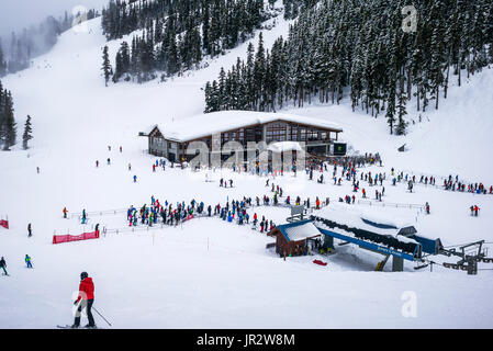 Downhill Skiiers At A Ski Resort Waiting In Line For The Chairlift; Whistler, British Columbia, Canada - Stock Photo