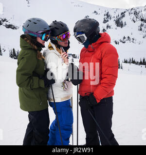 Three Young Adult Women Looking At A Cell Phone While Standing And Ready To Ski At A Ski Resort; Whistler, British - Stock Photo