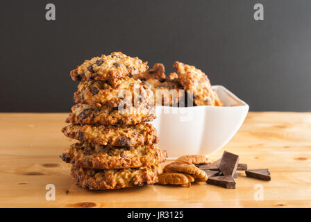 Stacked chocolate chip cookies, white bowl with cookies, pecan and pieces of chocolate on a black background - Stock Photo