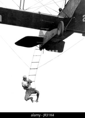'Fearless Freddie', a Hollywood stunt man, clinging to a rope ladder slung from a plane flown by A.M. Maltrup, about - Stock Photo