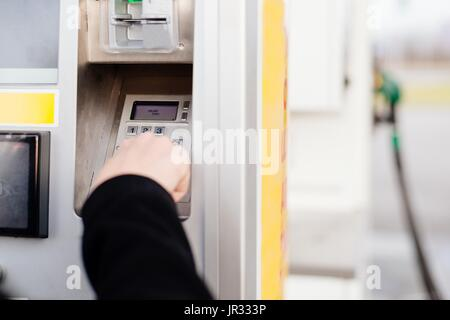 Woman paying with credit card for fuel on self service petrol station. Entering Pin Code - Stock Photo