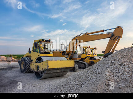 drum roller and excavators in construction site - Stock Photo