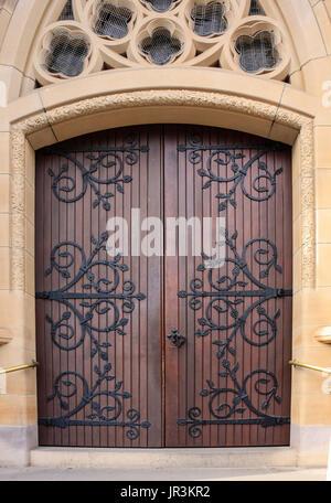 Decorative wooden church doors entrance set in sandstone brick - Stock Photo