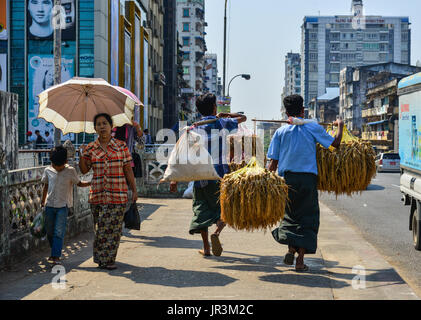 Yangon, Myanmar - Feb 13, 2017. People walking on street at downtown in Yangon, Myanmar. Yangon is Myanmar largest - Stock Photo