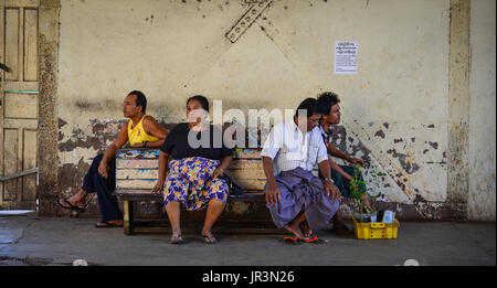 Yangon, Myanmar - Feb 13, 2017. Burmese people sitting at railway station in Yangon, Myanmar. Yangon is Myanmar - Stock Photo