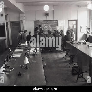 1950s, historical, science class studying earthworms, a group of male students sit on stools at the front of the class by the blackboard as teacher shows them samples, England, UK.