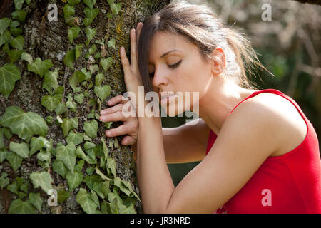 woman leaning against a tree - Stock Photo
