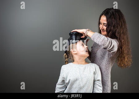 Mother and child playing together with virtual reality headsets - Stock Photo