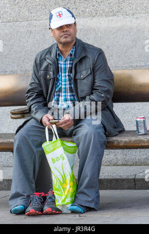 An asian male wearing an England baseball cap sitting by himself holding his mobile phone in London, UK. - Stock Photo