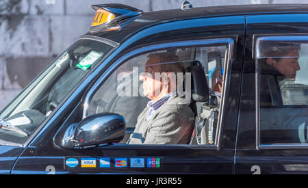 A black cab driver resting at the wheel in busy traffic in London with a male passenger behind him. The taxi has - Stock Photo