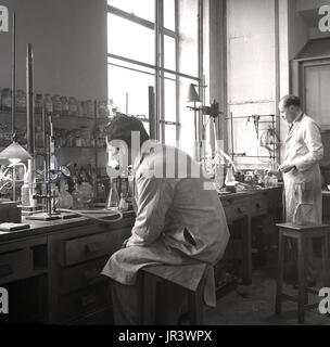 1950s, historical, male scientists in a laboratory conducting experiments, at a wooden workbench, England, UK.