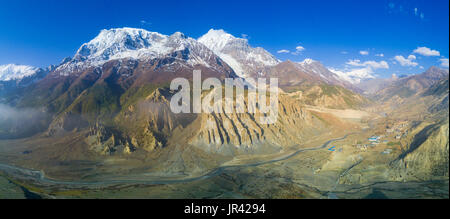 High altitude sweeping panoramic view of snow-capped Himalayan Annapurna mountain range and Manang Valley village - Stock Photo