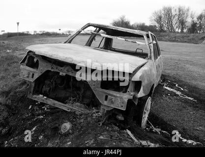 Burnt out abandoned motor car on the side of an isolated road. - Stock Photo