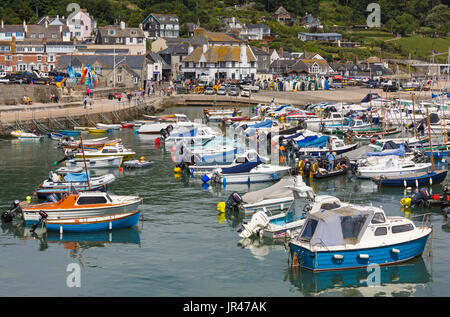 Boats in the harbour and Lyme Regis Town at Lyme Regis, Dorset in July - Stock Photo