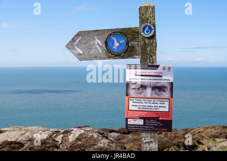 Isle of Anglesey Coastal Path and Wales Coast Path signs on a footpath signpost with a bilingual community safety - Stock Photo