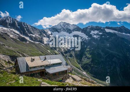Trekking in the Zillertal seen here with Kasseler Hut mountain refuge. - Stock Photo