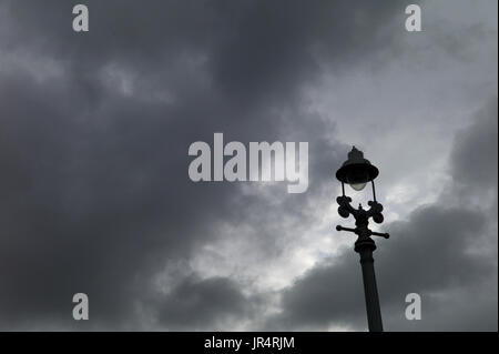 Old-fashioned lamppost silhouetted against stormy sky - Stock Photo