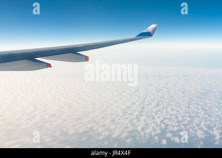 Winglet of an aircraft Airbus A330-300 of China Airlines CI-917 in flight, above stratocumulus clouds, against blue - Stock Photo