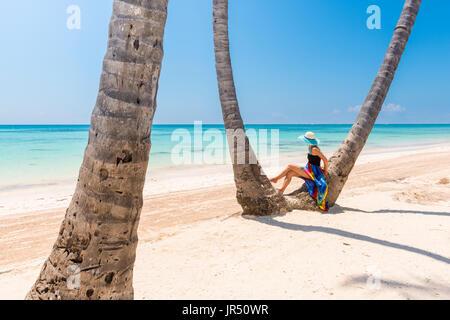 Juanillo Beach (playa Juanillo), Punta Cana, Dominican Republic. Woman under high palm trees on the beach. - Stock Photo