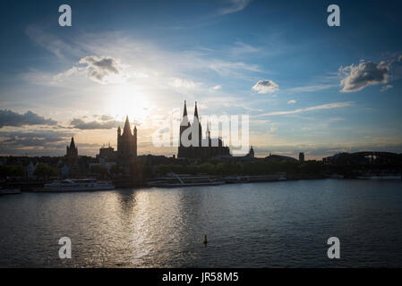 Light atmosphere on the Rhein bank with the silhouette of the Cologne Cathedral and the church Groß St. Martin, - Stock Photo