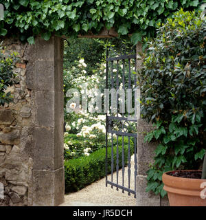 Open gate leading to a rose garden - Stock Photo