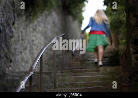 An unidentified young woman walks on away from camera up a set of steep steps. (posed by model) - Stock Photo