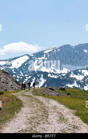 Four mountaineers on the mountain trail - Stock Photo