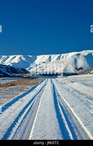 Hawkdun Range and snowy track to Falls Dam, Maniototo, Central Otago, South Island, New Zealand - Stock Photo